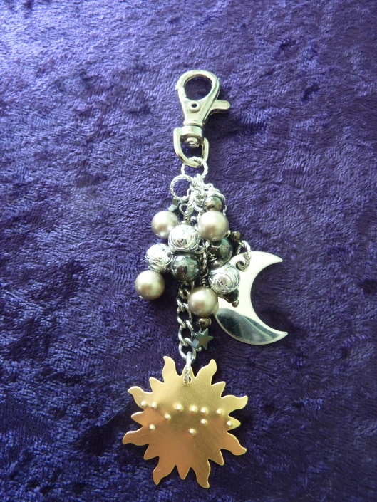 "A purse charm with a sun, moon, and stars motif. The word ""Shine"" is written in braille"